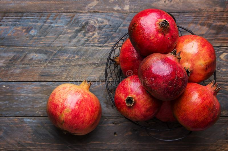Ripe juicy organic vibrant red pomegranates in metal wicker basket on reclaimed plank barn wood background. Fall produce harvest royalty free stock images
