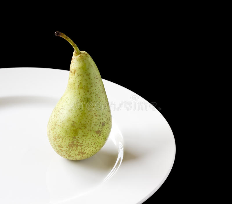 Ripe juicy pear on white plate