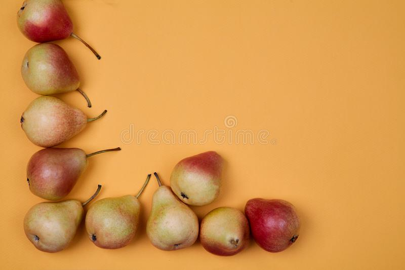 Ripe juicy pears placed on orange background. Colorful fruit pattern or background. stock photography
