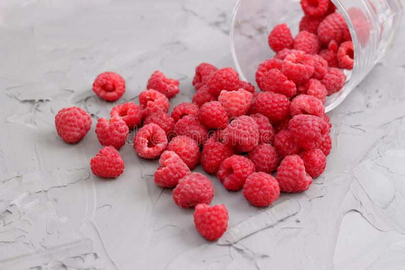 Ripe juicy raspberry crumbled out of a glass royalty free stock photo