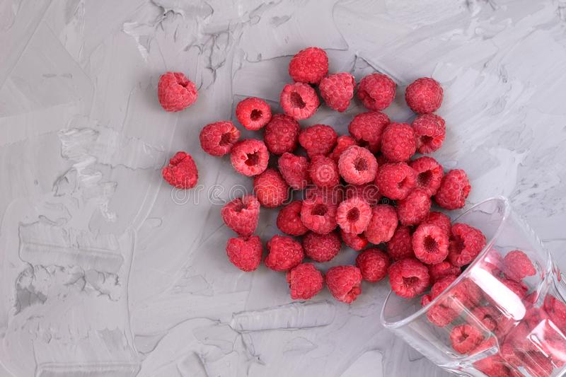 Ripe juicy raspberry crumbled out of a glass royalty free stock photography