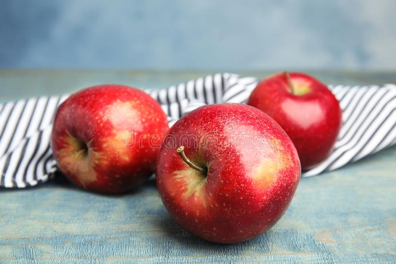 Ripe juicy red apples on wooden table against blue background. Closeup royalty free stock images