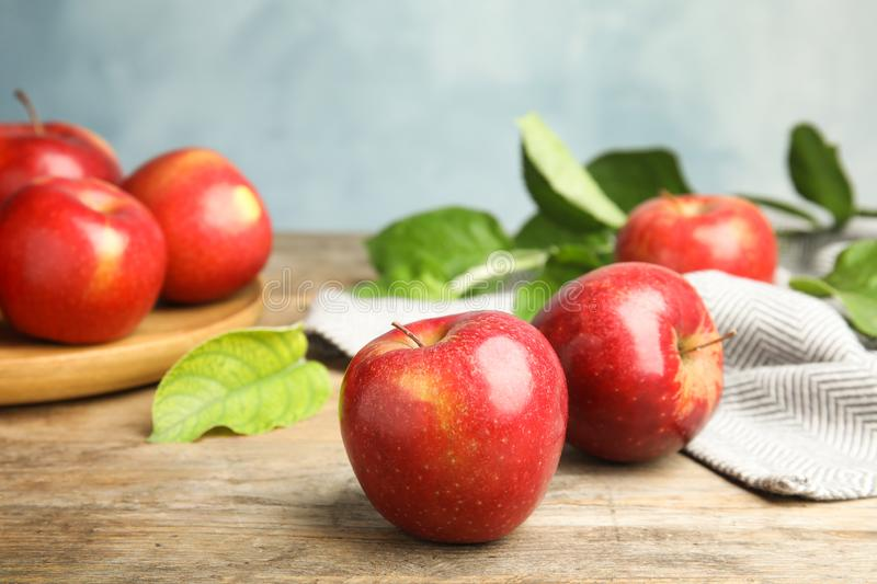 Ripe juicy red apples on wooden table against blue background. Space for text stock photos