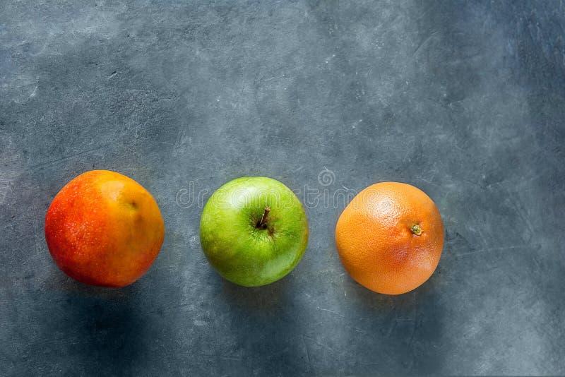 Ripe juicy seasonal and tropical fruits mango grapefruit apple on dark stone background. Healthy plant based diet vitamins detox stock images