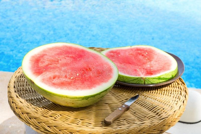 Ripe Juicy Seedless Watermelon Cut in Half Slices on Plate on Rattan Table by Swimming Pool. Sunlight. Seaside Vacation Relaxation royalty free stock photos