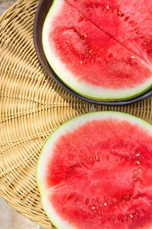 Ripe Juicy Seedless Watermelon Cut in Half Slices on Plate on Rattan Table by Swimming Pool. Sunlight. Vacation Relaxation Summer royalty free stock images