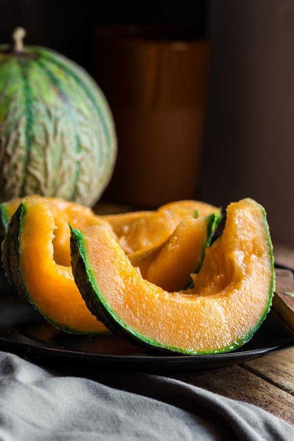 Ripe juicy sliced orange cantaloupe, dark plate, knife, wood kitchen table, rustic interior royalty free stock photos