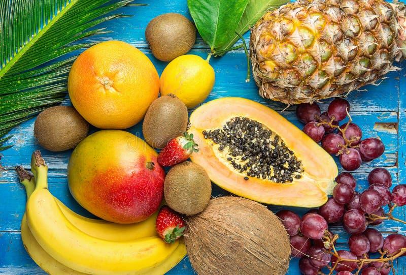 Ripe Juicy Tropical Summer Seasonal Fruits Mango Papaya Pineapple Coconut Kiwi Bananas Strawberries Grapes Citrus on Palm Leaf. Ripe Juicy Tropical Summer royalty free stock photography