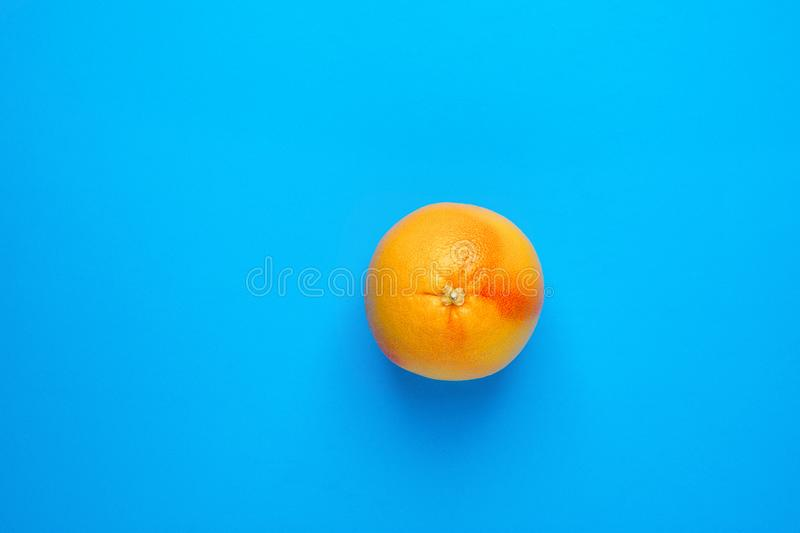 Ripe Juicy Whole Grapefruit on Solid Blue Background. Vitamin C Healthy Diet Summer Detox Vegan Tropical Fruits Concept royalty free stock photo