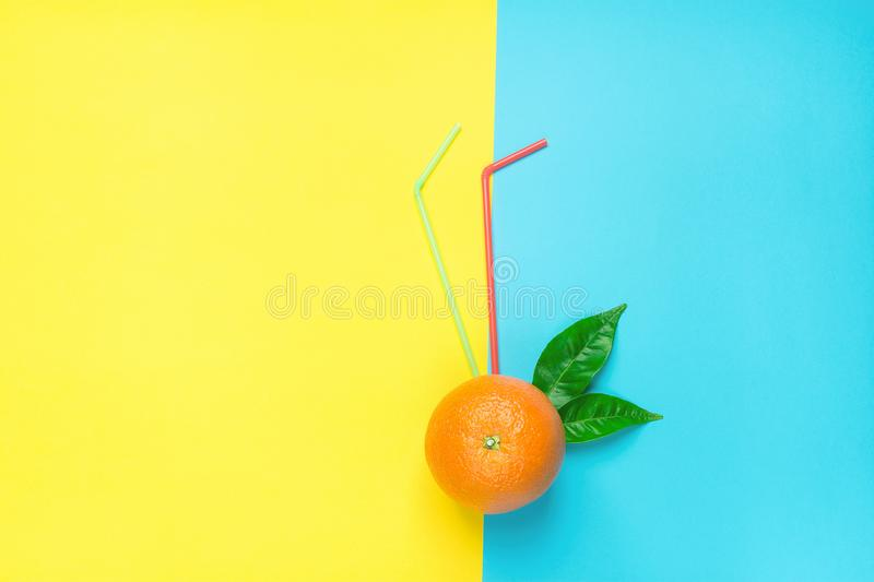 Ripe Juicy Whole Orange with Green Leaves Drinking Straws on Duotone Yellow Blue Background. Fresh Juices Summer Cocktails stock images