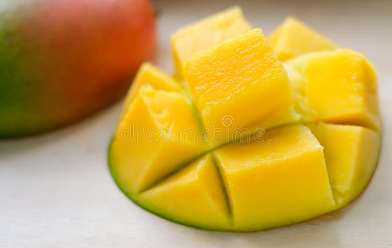 Ripe juicy yellow exotic mango cut into cubes on wooden background. Tropical delicacy full of vitamins for a healthy royalty free stock photo