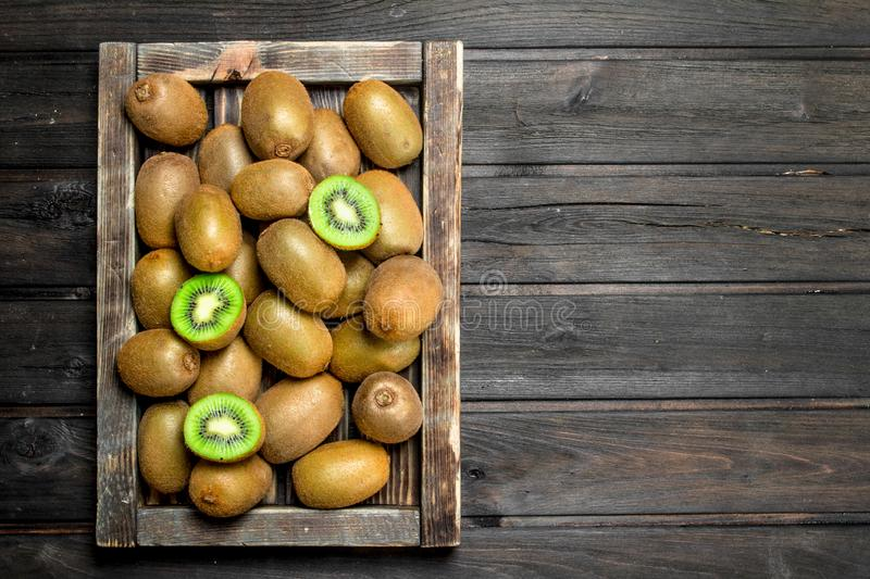 Ripe kiwi fruit in a wooden tray. On wooden background stock photography