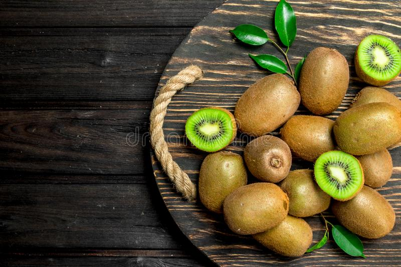 Ripe kiwi with leaves on a wooden tray. On black wooden background stock images