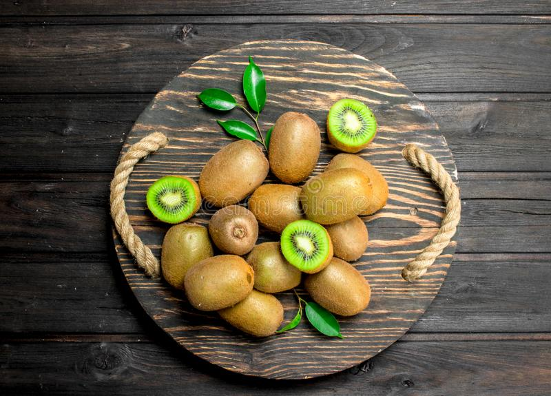 Ripe kiwi with leaves on a wooden tray. On black wooden background stock image