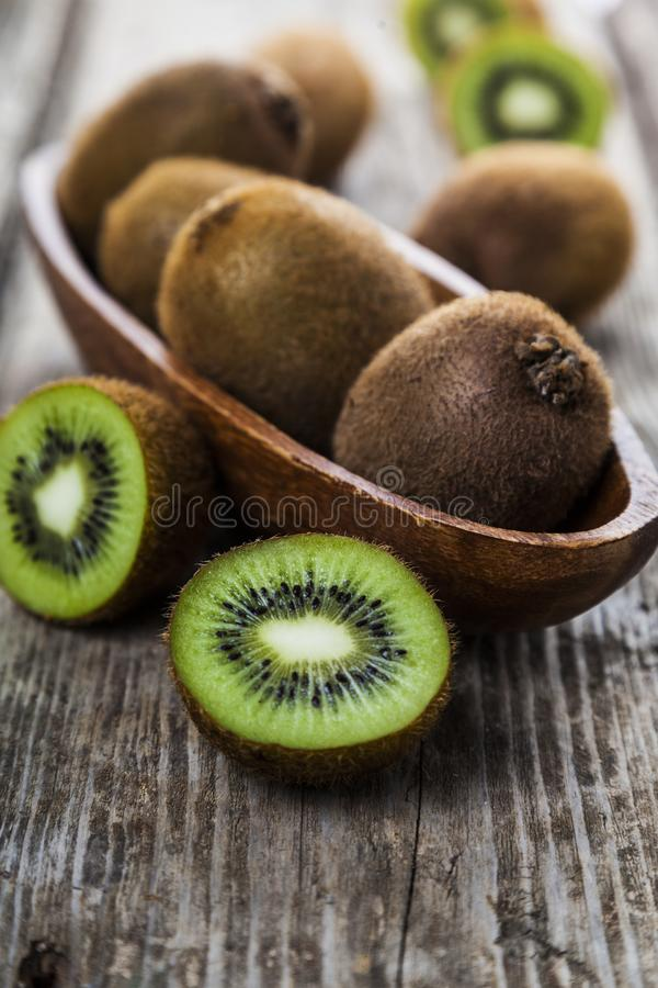 Ripe kiwi in a wooden dish. On a wooden background. Healthy eating stock images