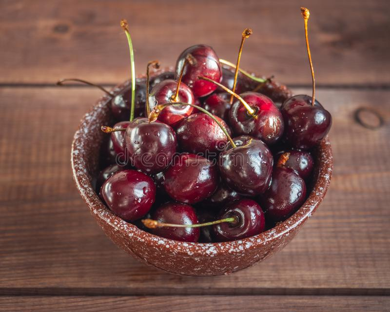 Ripe large sweet cherries in a deep ceramic brown bowl on an wooden tray. Shot from close range royalty free stock images