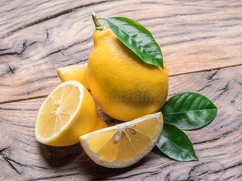 Ripe lemon with lemon leaves on old wooden table. Close-up. stock photography
