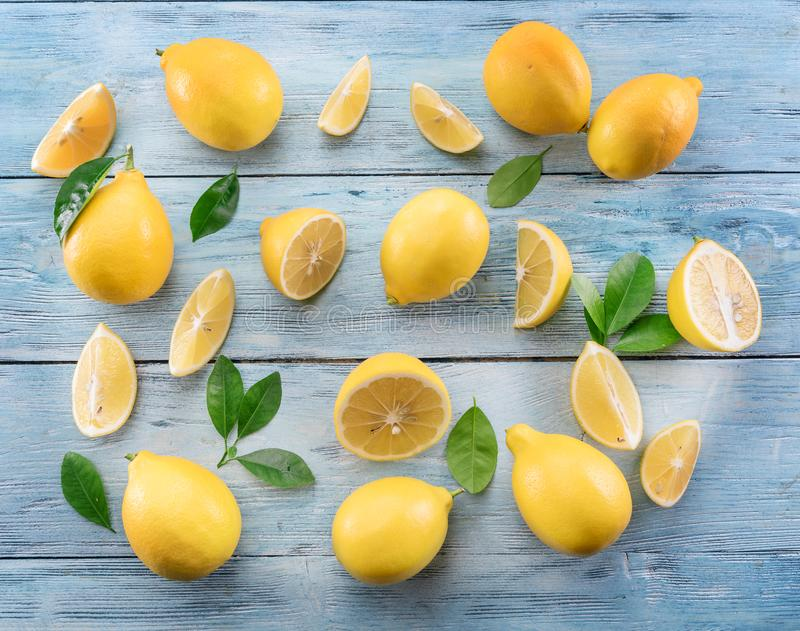 Ripe lemons and lemon leaves on blue wooden background. Top view royalty free stock images