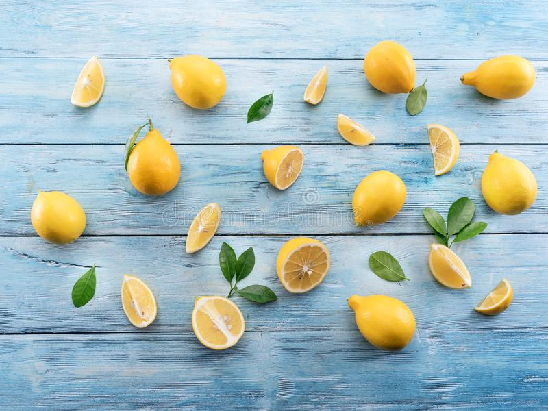 Ripe lemons and lemon leaves on blue wooden background. Top view stock photos