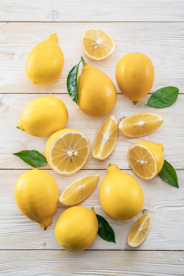 Ripe lemons and lemon leaves on wooden background. Top view. stock photos