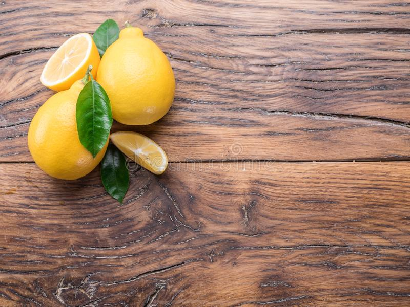 Ripe lemons and lemon leaves on wooden background. Top view. royalty free stock photos