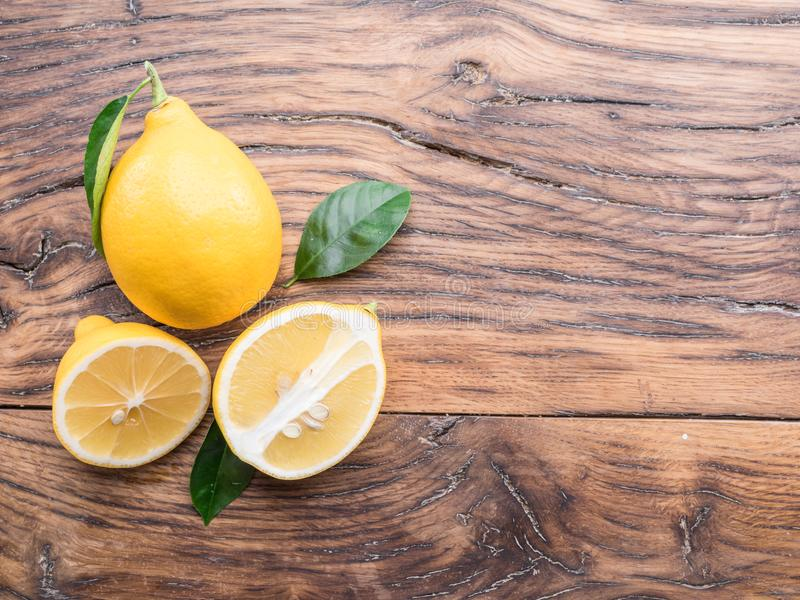 Ripe lemons and lemon leaves on wooden background. Top view. stock photo