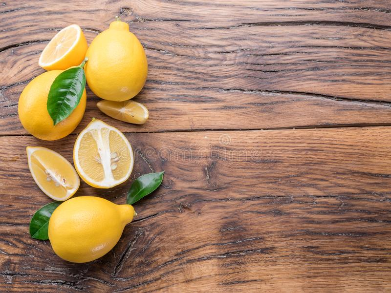 Ripe lemons and lemon leaves on wooden background. Top view. stock photography