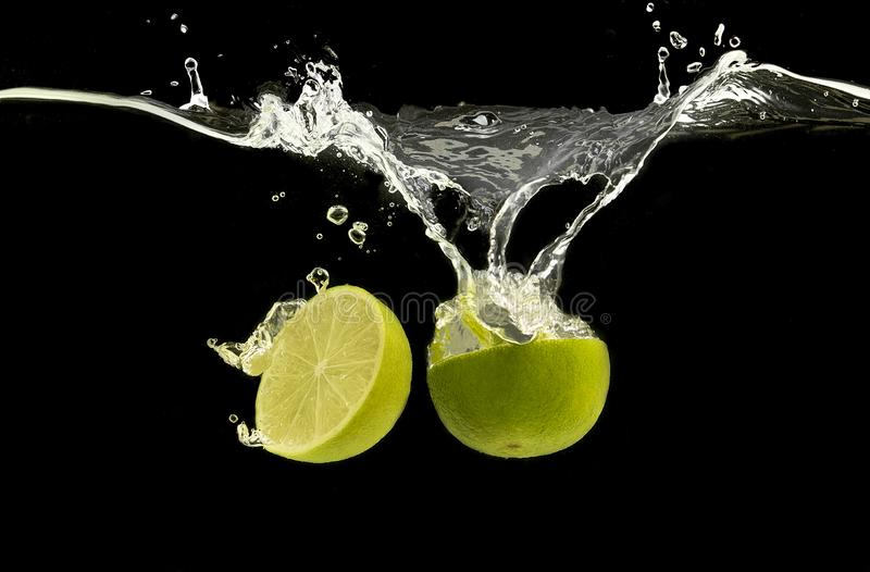 Ripe lime halves splashing in clear water royalty free stock photos
