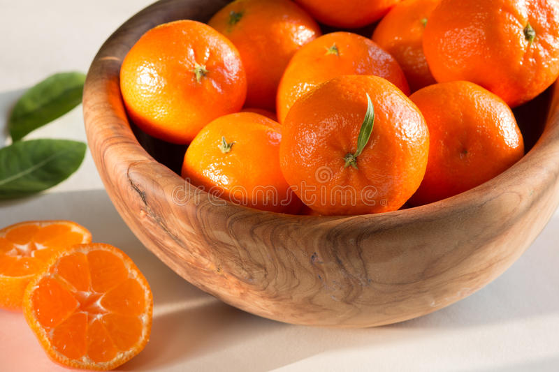 Ripe mandarins in a wooden bowl , cut , with green leaves stock photo