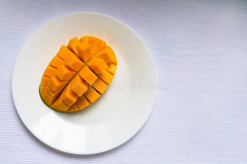 Ripe mango diced on a white plate. Copy space. royalty free stock photos