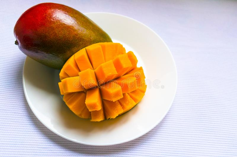 Ripe mango diced on a white plate. Copy space. stock image