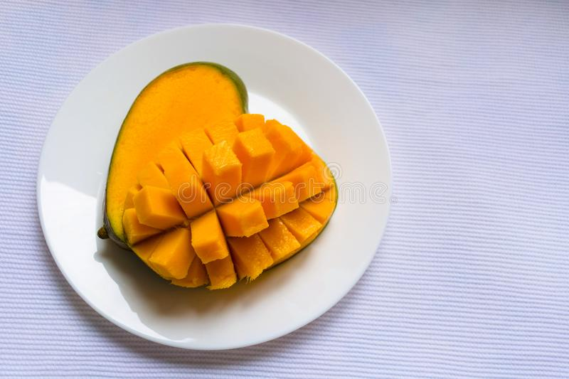 Ripe mango diced on a white plate. Copy space. royalty free stock photography