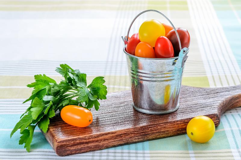Ripe multicolored mini tomatoes in a small metal bucket and parsley over brown wooden cutting board on a tablecloth. Vegetables,. Vegetarian and healthy eating stock images