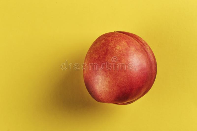 One nectarine on a bright background. Ripe nectarine on a yellow background, space for text royalty free stock photos