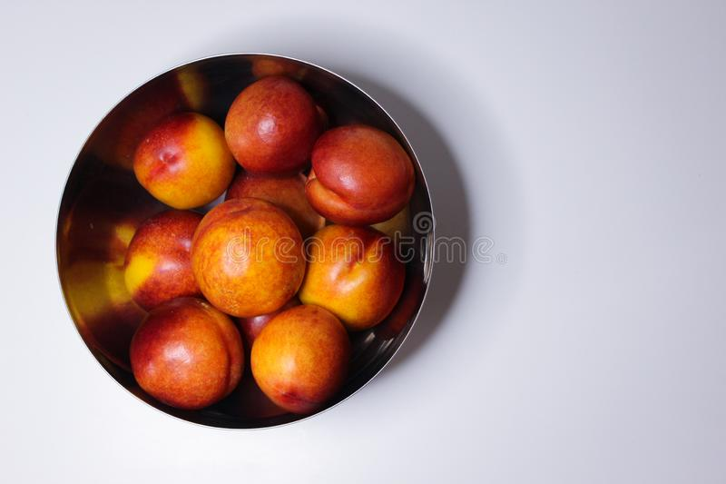 Ripe nectarines in a metal plate on a white background. Healthy eating royalty free stock images