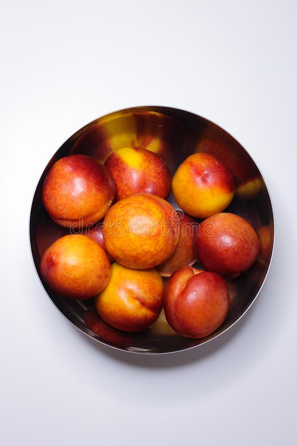 Ripe nectarines in a metal plate on a white background. Healthy eating stock image