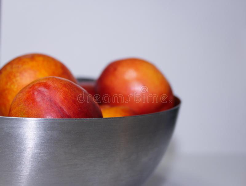 Ripe nectarines in a metal plate on a white background. Healthy eating royalty free stock photography