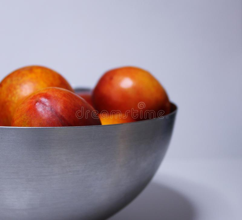 Ripe nectarines in a metal plate on a white background. Healthy eating stock images