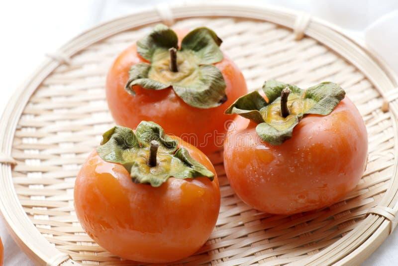 Fresh kaki on basket.Ripe orange persimmon fruit. Ripe orange persimmon fruit.fresh kaki with bamboo basket on white background stock photos