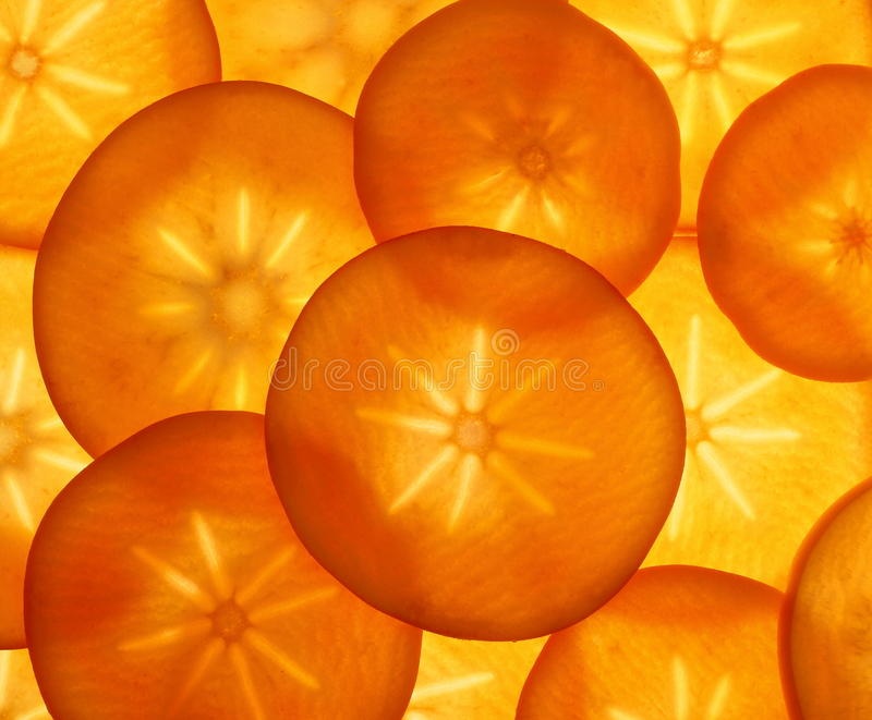 Ripe orange persimmon fruit slices as food background. Top view royalty free stock images