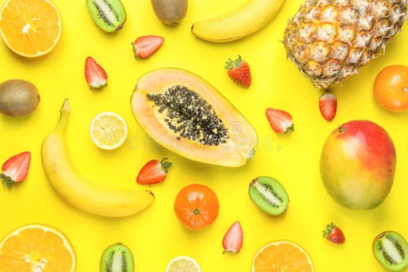 Ripe Organic Cut in Half Strawberries Kiwi Pineapple Mango Papaya Citrus Fruits Bananas Pattern on Yellow Background. Bright Sunny stock image