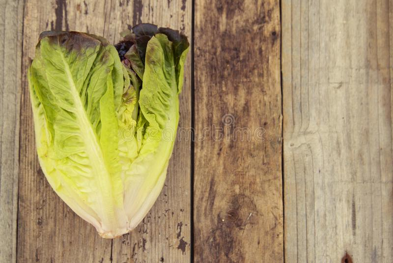 Ripe organic green salad Romaine lettuce leaves, on wooden board. Copy space. Healthy food. royalty free stock images
