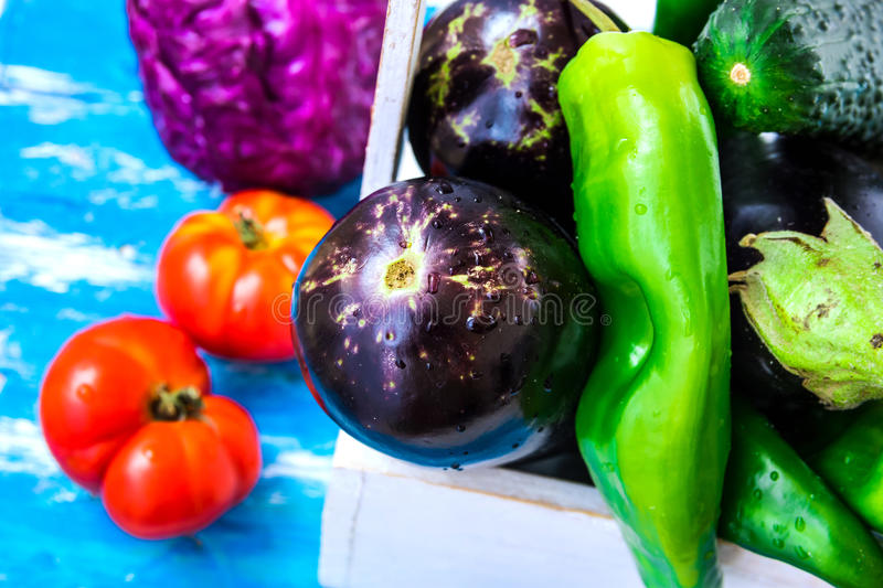 Ripe organic purple eggplants, fresh green italian peppers in wood box, tomatoes, cabbage on blue wood background, clean eating. Vegetarian, harvest gardening royalty free stock photos