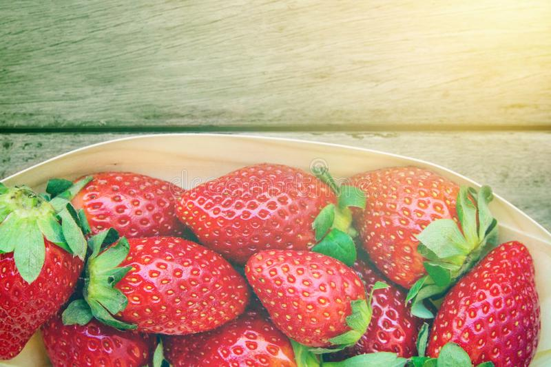 Ripe organic strawberries on aged plank wood background in golden sunlight. Summer fruits and berries local produce stock photography