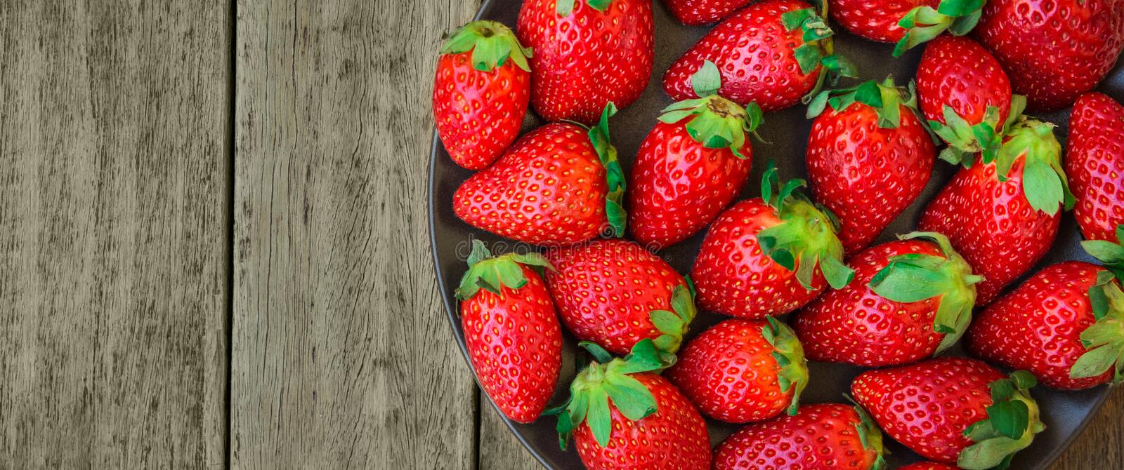 Ripe organic strawberries on aged plank wood background. Summer fruits and berries local produce vitamins plant based diet concept. Long banner with copy space royalty free stock photo