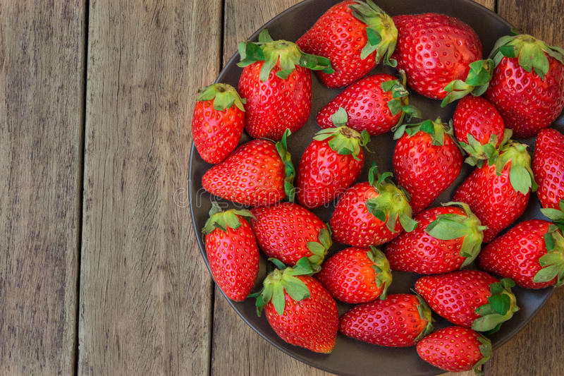 Ripe organic strawberries on dark plate on plank wood background, close up, healthy food, detox stock photos