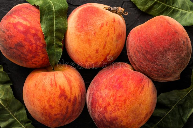 Ripe peaches on black stone background. Healthy food concept. Top view, macro royalty free stock photos