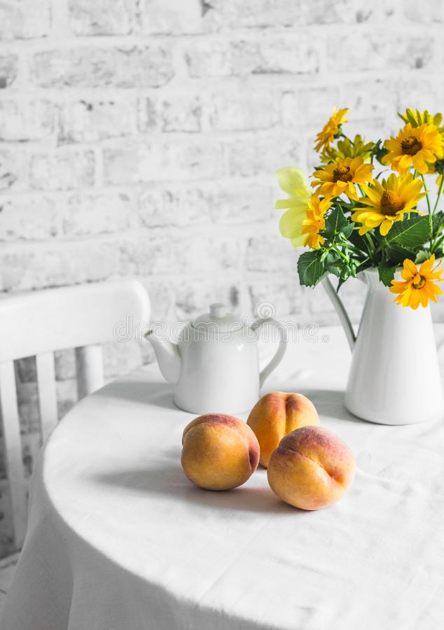 Ripe peaches and a bouquet of yellow flowers on the table on a light background. Cozy home kitchen still life stock image