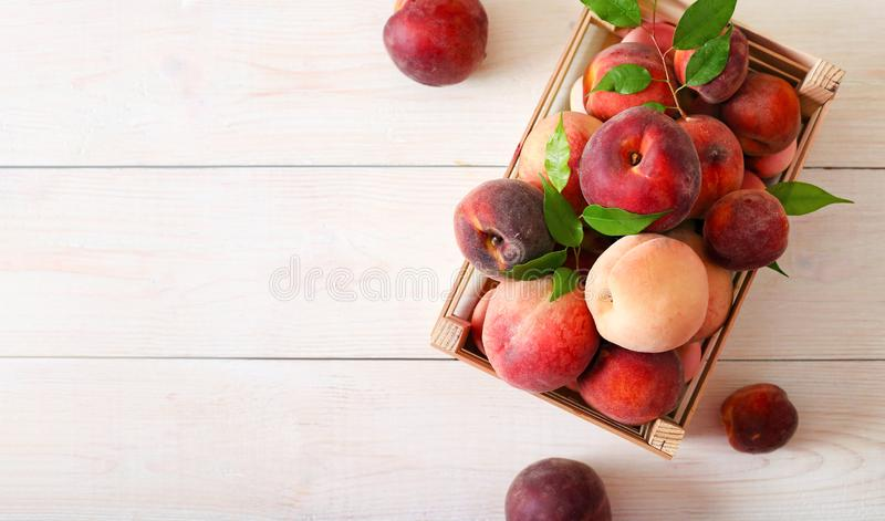 Ripe peaches in a box on wooden background top view. Ripe red peaches in a wooden box on a light background top view. Healthy fruit peach scattered on a wooden stock images