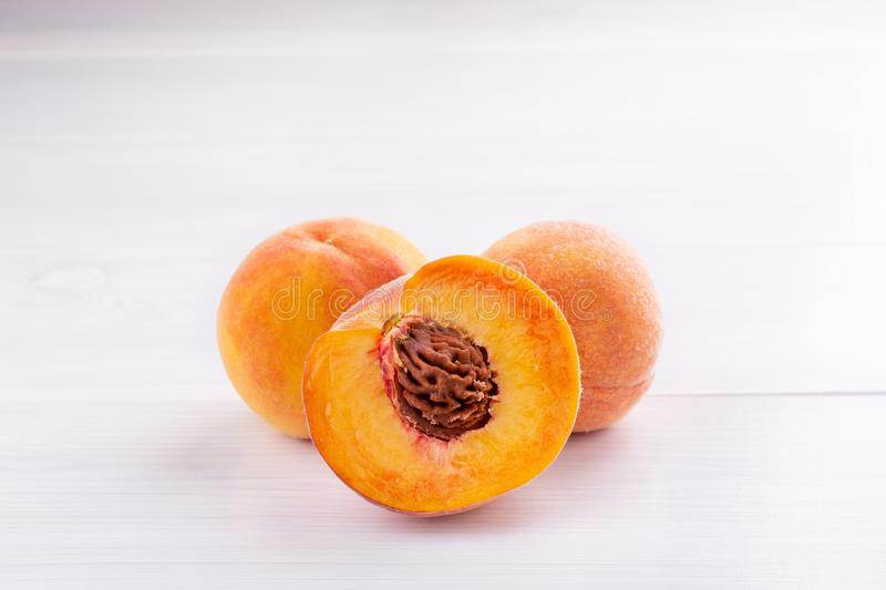 Ripe peaches close-up on a white wooden background royalty free stock images